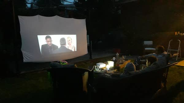 A video projector set up, projecting a movie in the dark in someone's back yard.