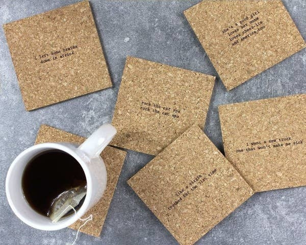 """A set of six cork coasters with lyrics from 80s songs with mistaken lyrics, such as """"rock the cat spa, rock the cat spa"""" and a tea cup on one of them"""