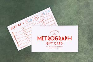 $50 Metrograph gift card against green surface