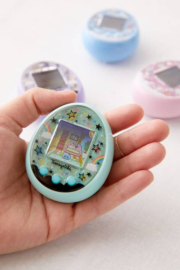 Hands holding a blue pastel Tamagotchi ON game.