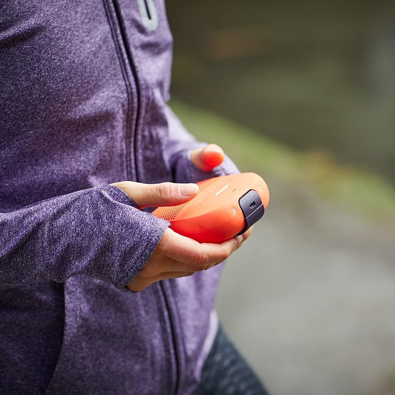 Una modelo sostiene una bocine Bosé Bose SoundLink Micro de color naranja