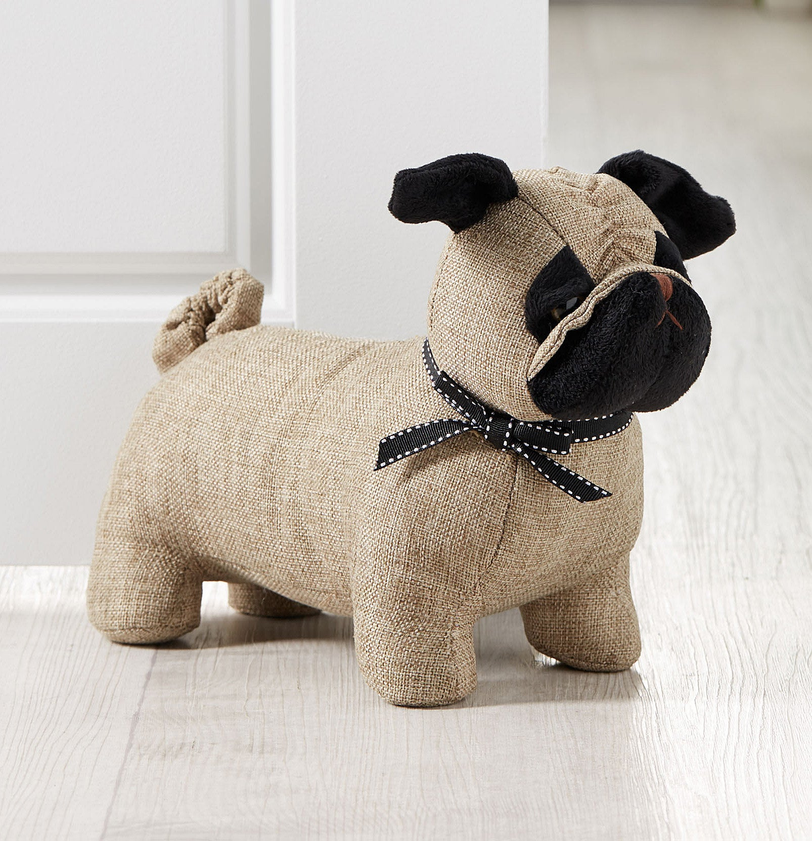 A dog-shaped door stopper holding open a door