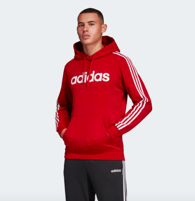 "Model wearing the red version, which has ""Adidas"" written across the chest and a large front pocket pouch"