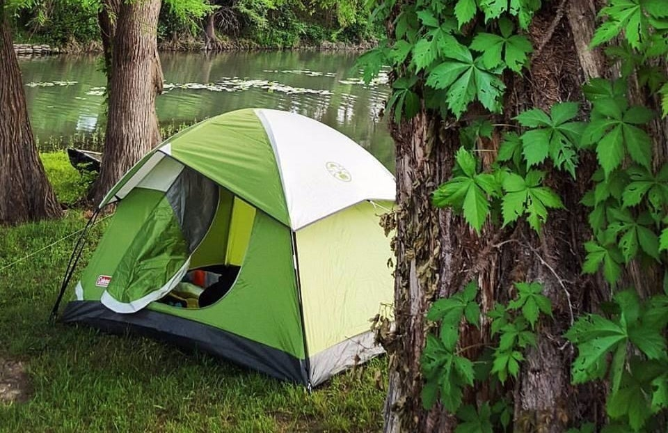 A small light green tent set up in a wooded area