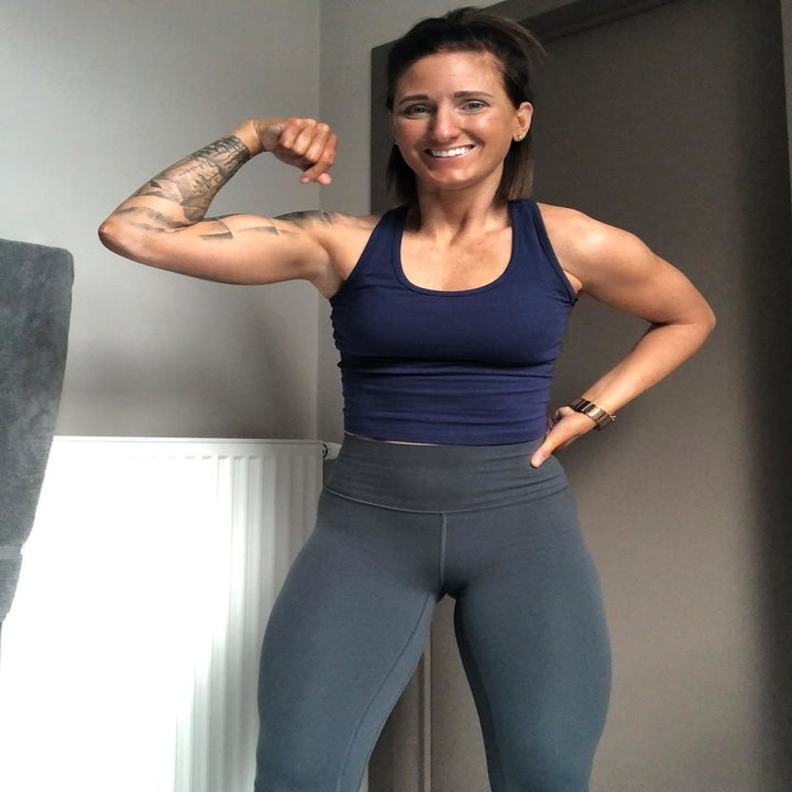 Reviewer wearing tank top and flexing