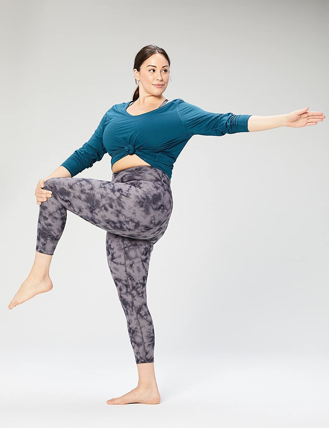 Model wearing the 7/8 grey leggings while holding a yoga pose