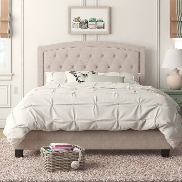 A made-bed resting on an upholstered platform with a matching rounded and tufted headboard