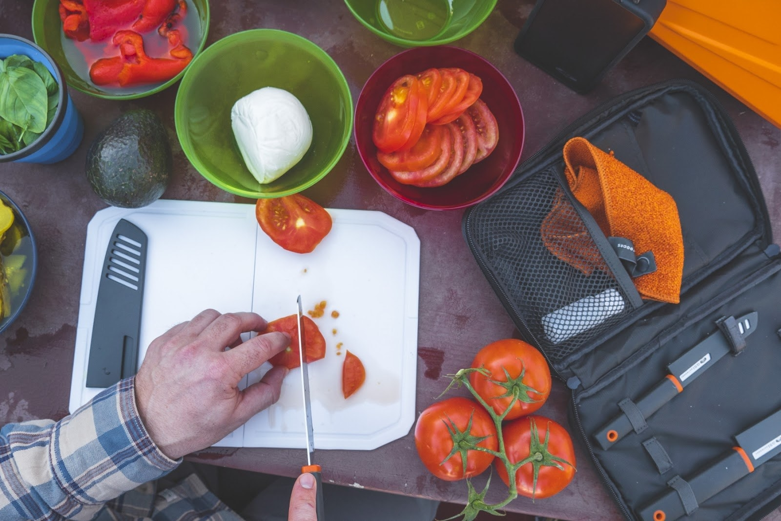 Hands slicing a tomato with the chef's knife and cutting board