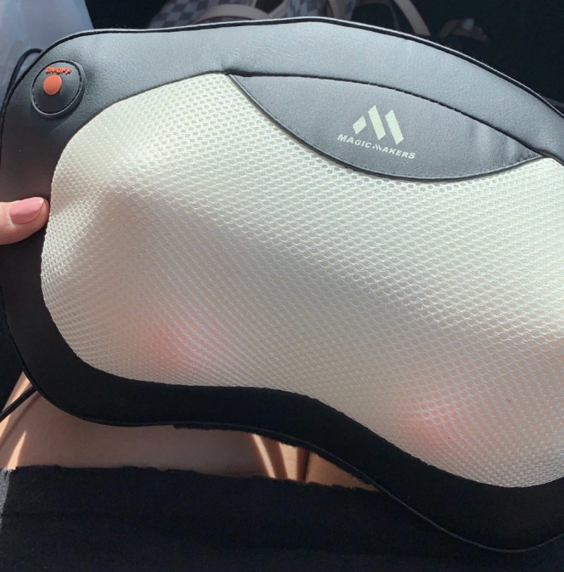 A reviewer holding the massager, which has three rotating heated balls under the fabric on both sides