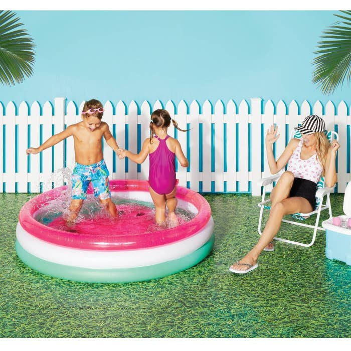 Two kids playing around in an inflatable mini pool with a watermelon design.