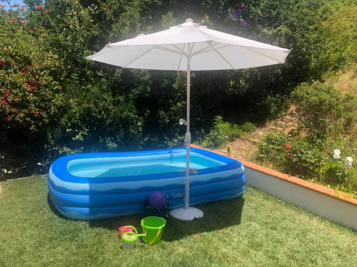 A rectangular inflatable pool in a backyard under an umbrella