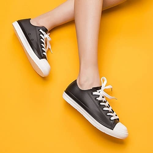 model wearing black low top sneakers with white laces