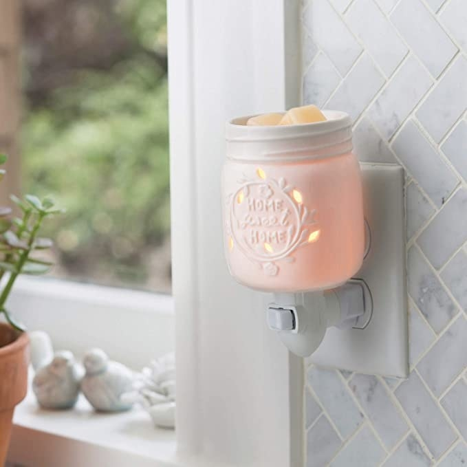"""the wax warmer is plugged into a wall near a window. It's shaped like a mason jar and says """"home sweet home"""" on the front."""