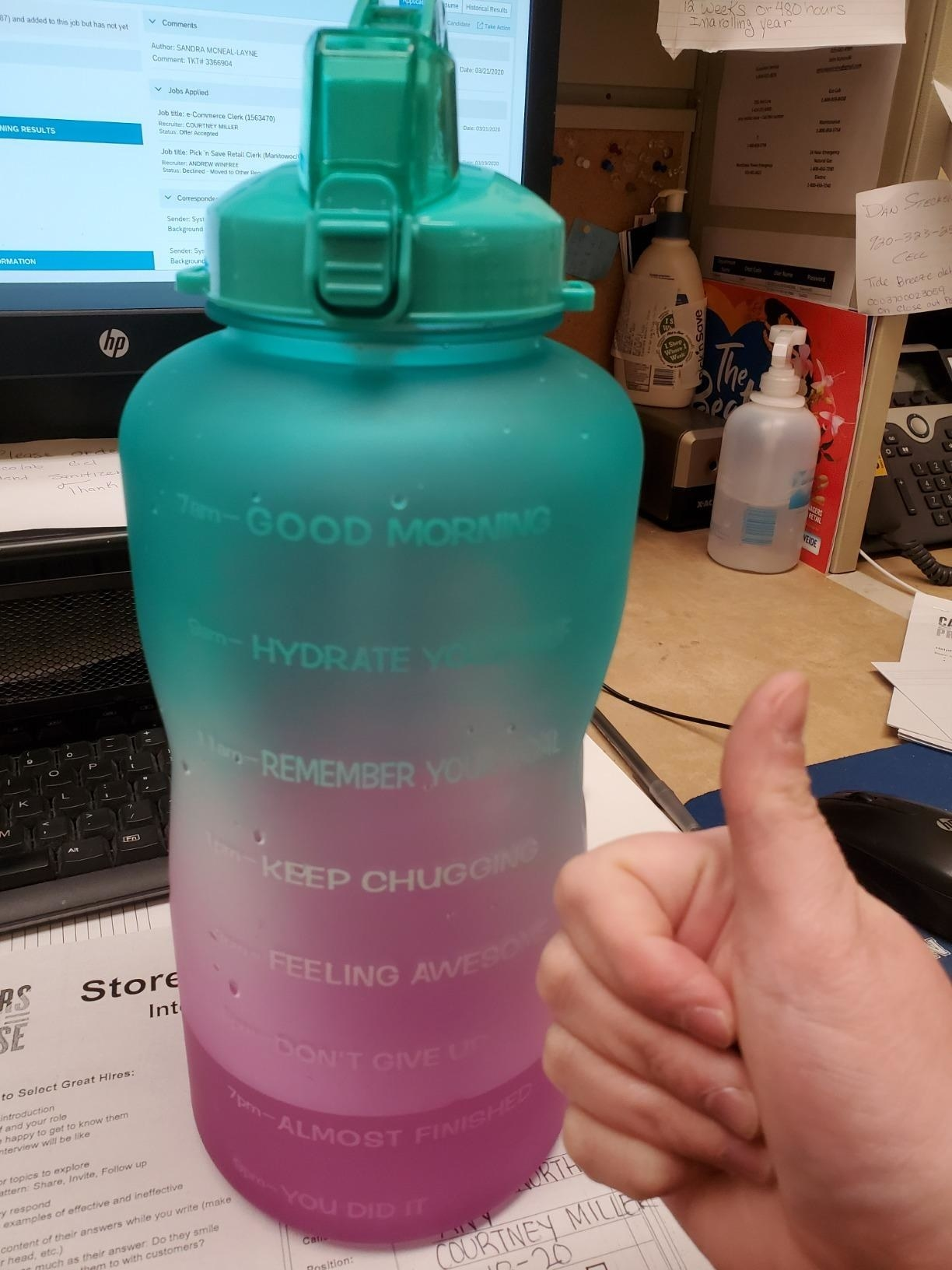 A pink and blue gradient water bottle with timestamps and motivational phrases on the side