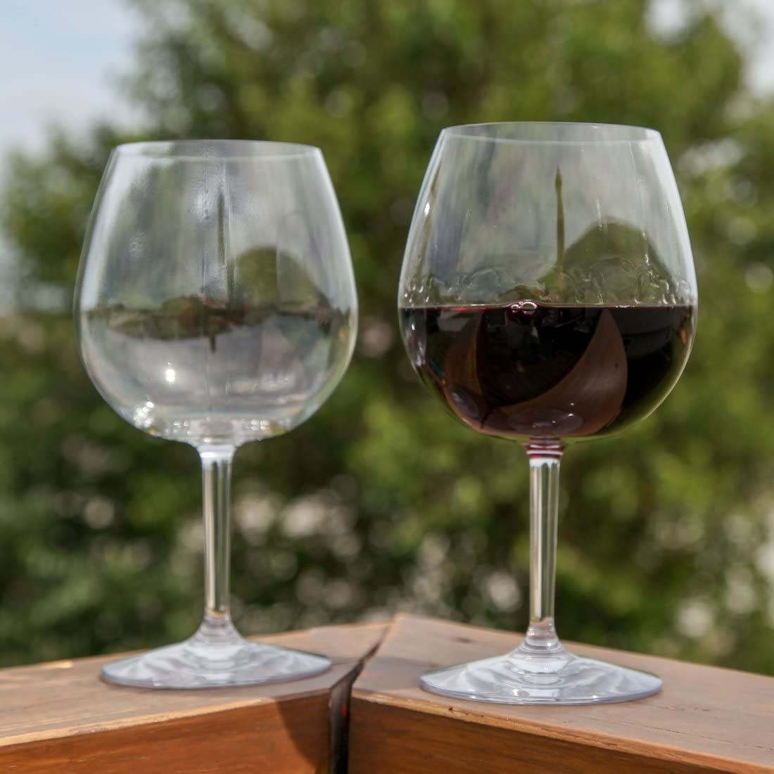 A close-up of the two balloon glasses where one is half-full of wine