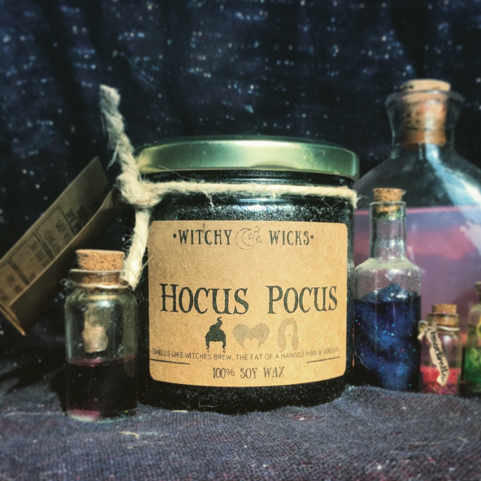 """a black candle with a tin twist-off lid and a label that says """"hocus pocus"""" with three heads of the witches on it"""