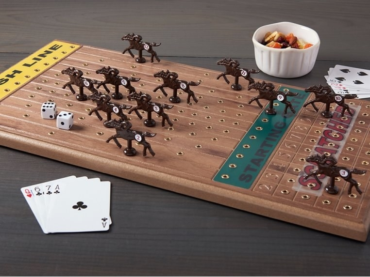 a dark wood board with pegged horses, dice, and cards