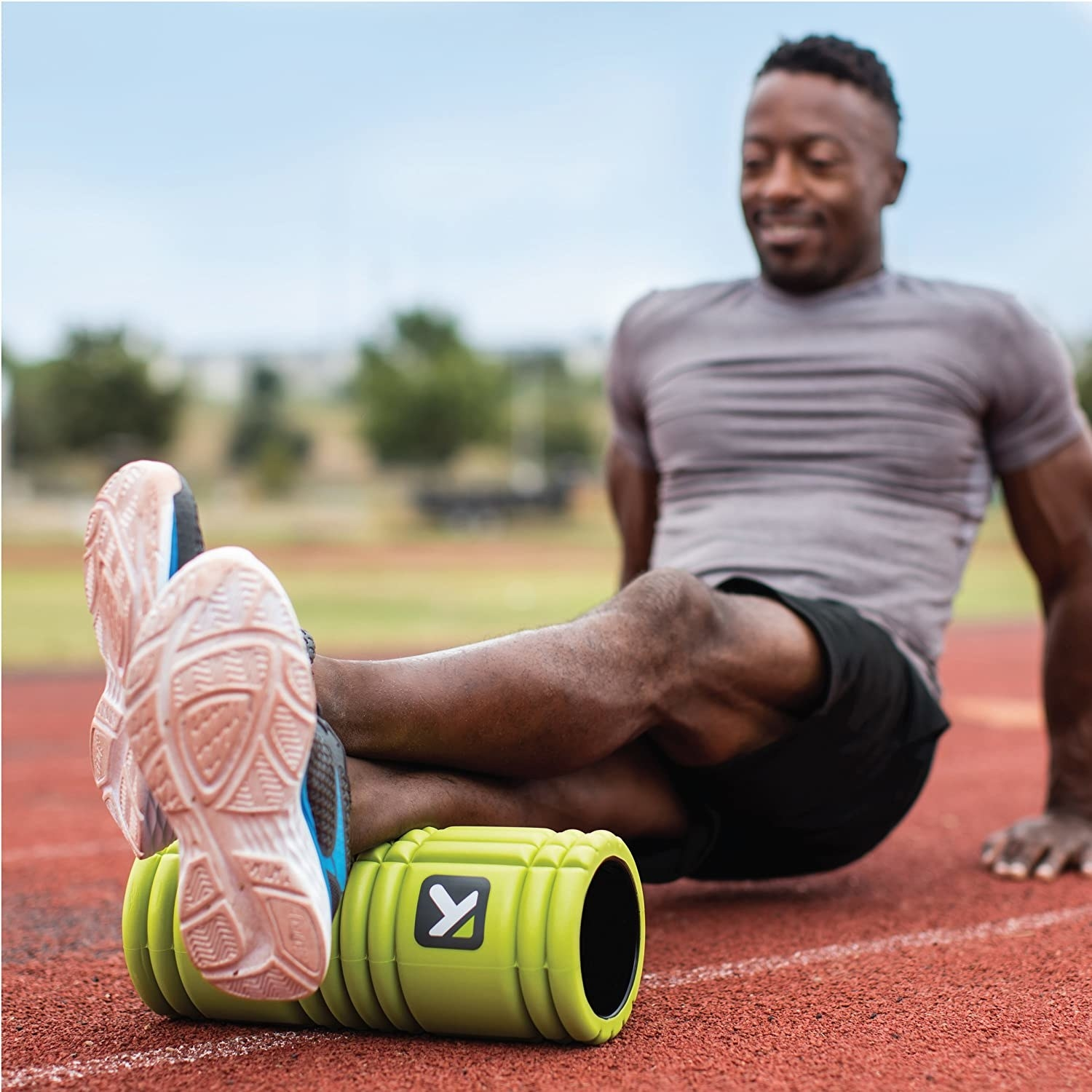 A model stretching their legs on a lime green foam roller
