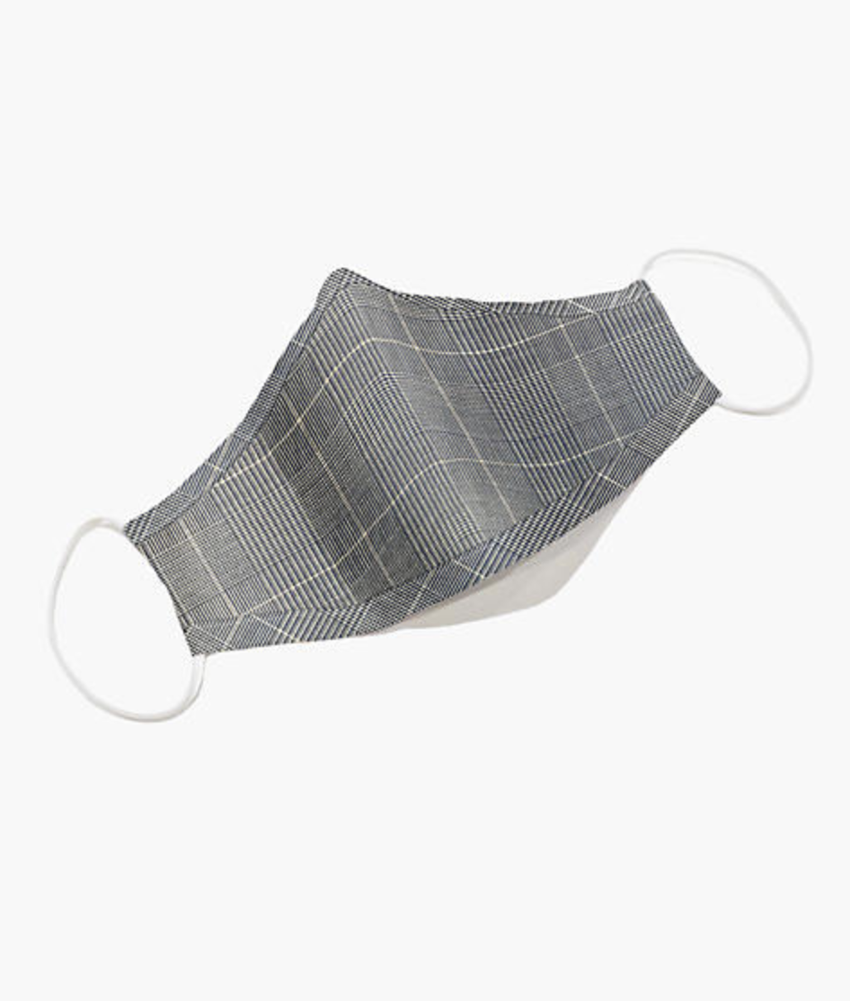 A blue and gray plaid face mask with white elastic ear loops