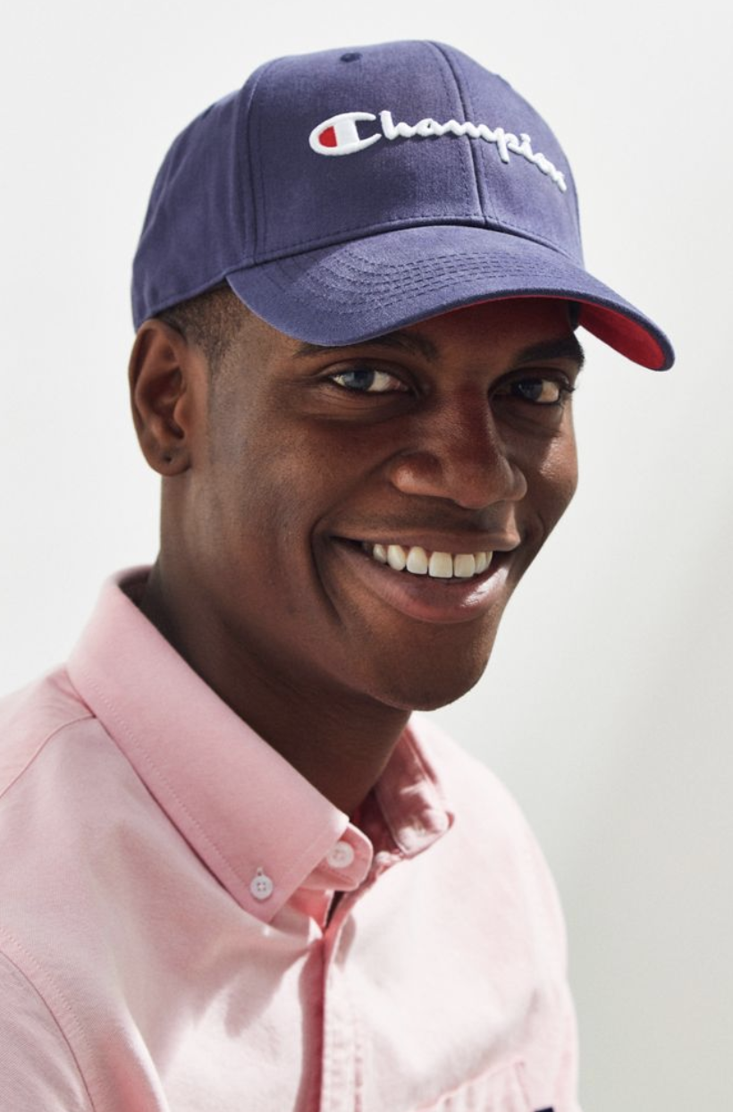 Model wears navy Champion baseball cap with a pink shirt