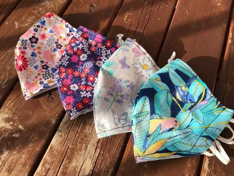 Four folded face masks in bright prints