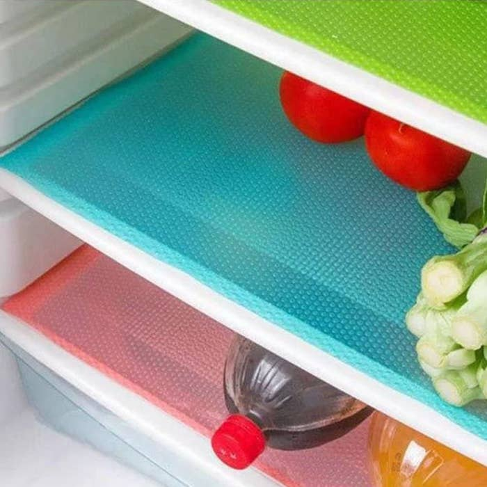 Food and a bottle resting on coloured sheets of plastic that lines fridge shelves
