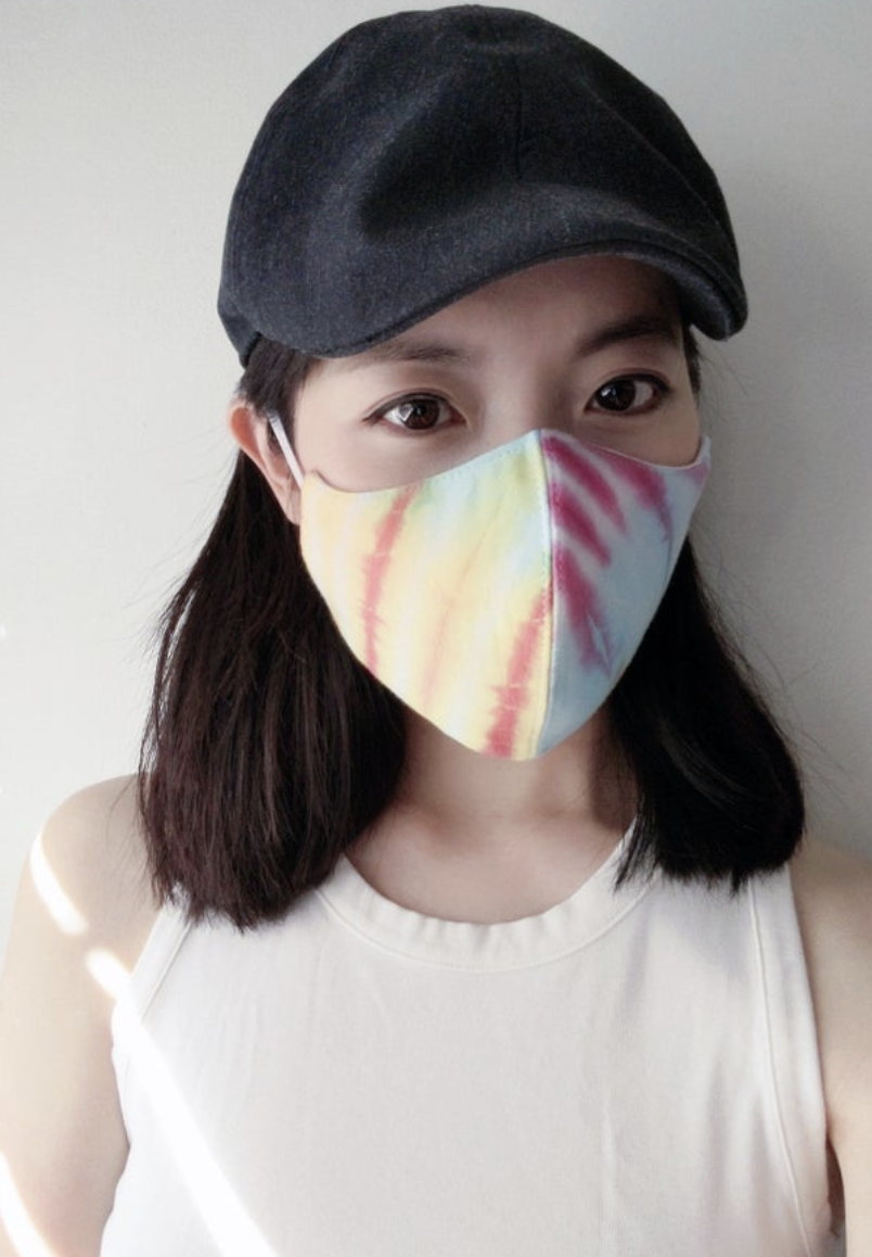 Model wears a tie-dye face mask with a white tank top and black hat
