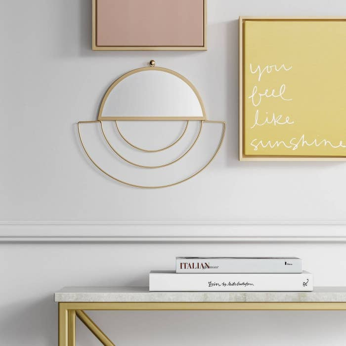 Half-round wall mirror with gold open-wired accents around the base hanging on a wall