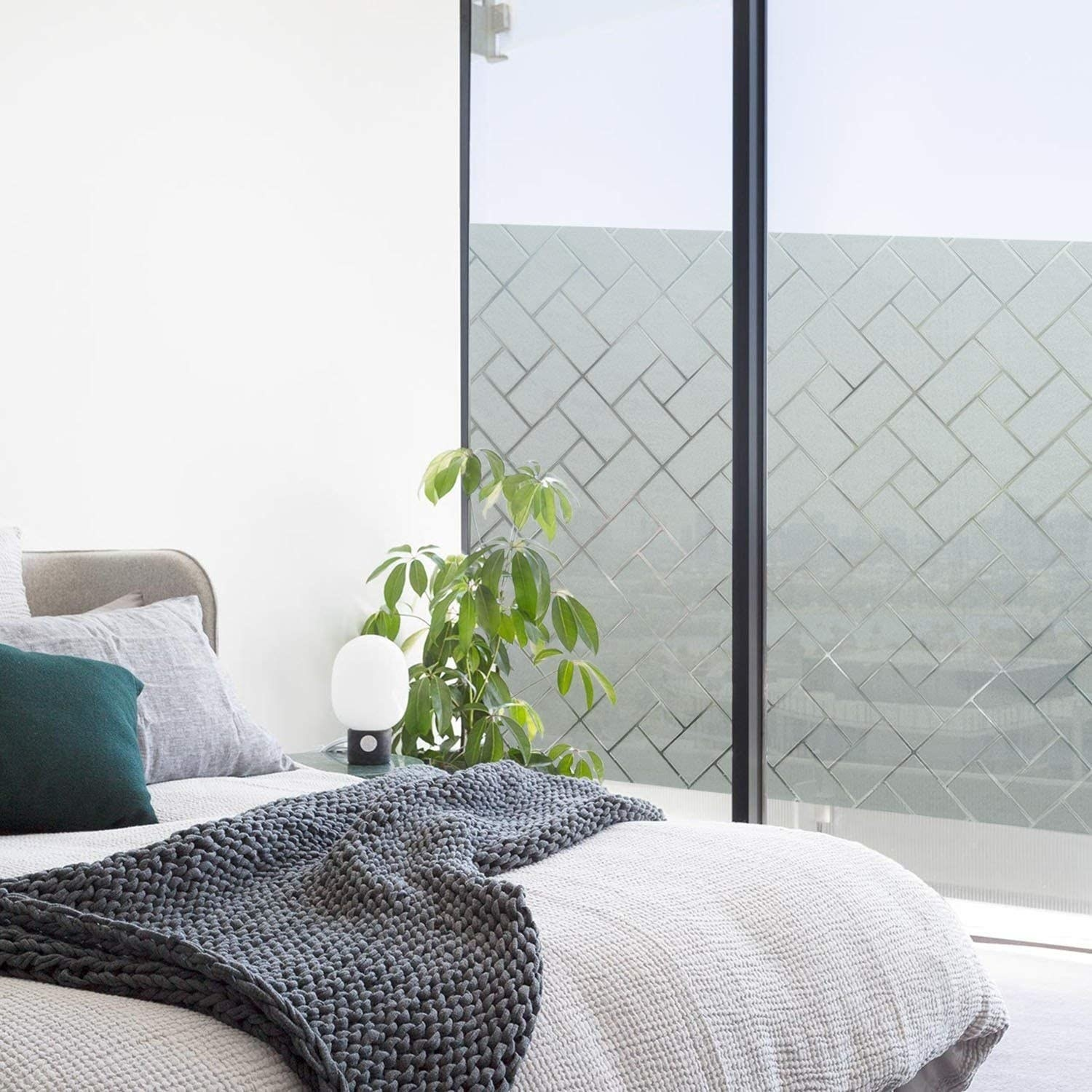 Bedroom with the privacy film with a rectangle design on a large window