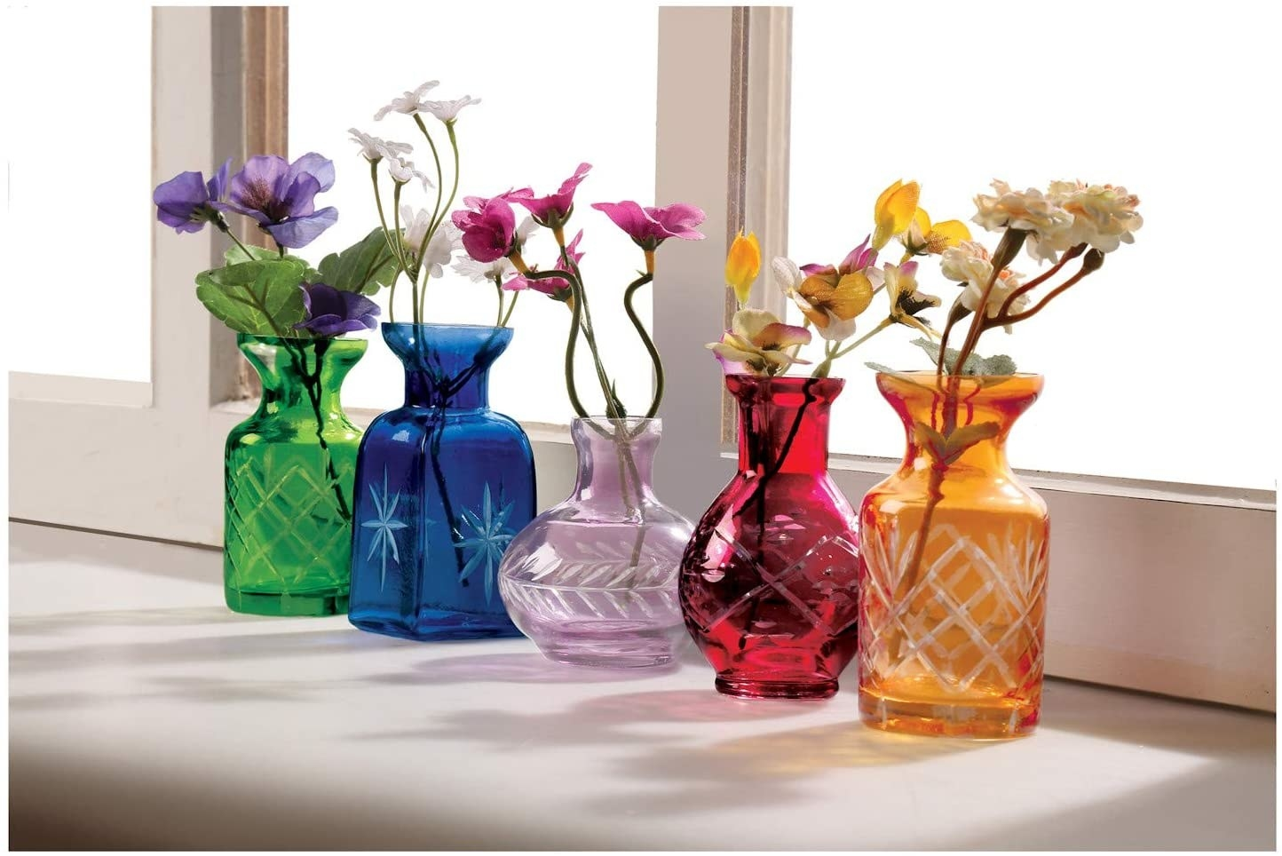 Five small glass vases in different sizes with etching on the bases in green, blue, purples, red, and orange