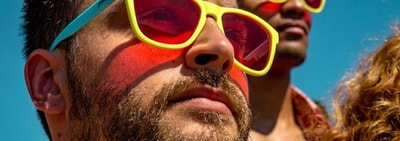 Two models wearing yellow and blue colorblocked sunglasses with tinted lenses