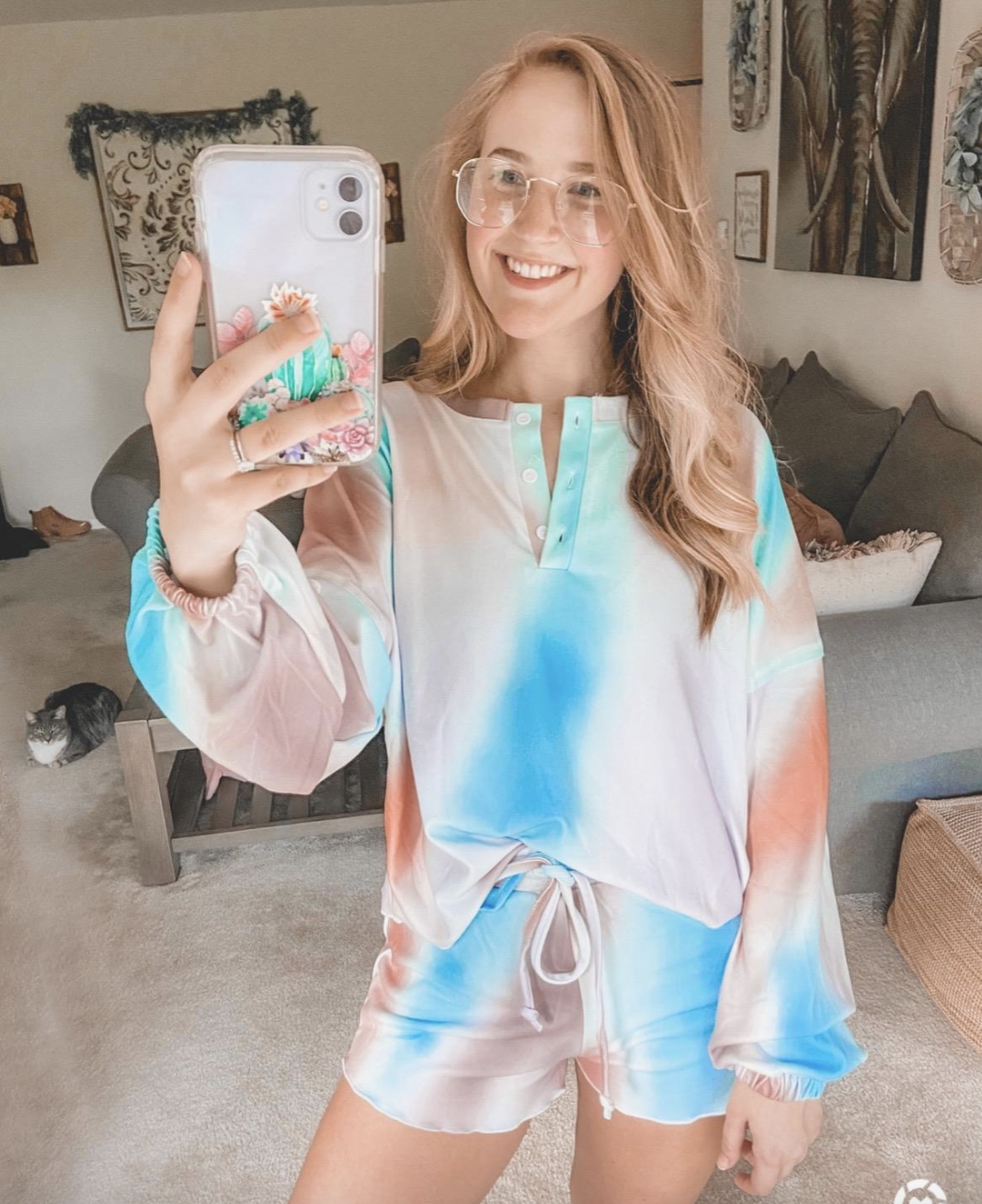 reviewer wearing drawstring shorts and V-neck sleeved top in tie dye pattern with pink, blue, and orange