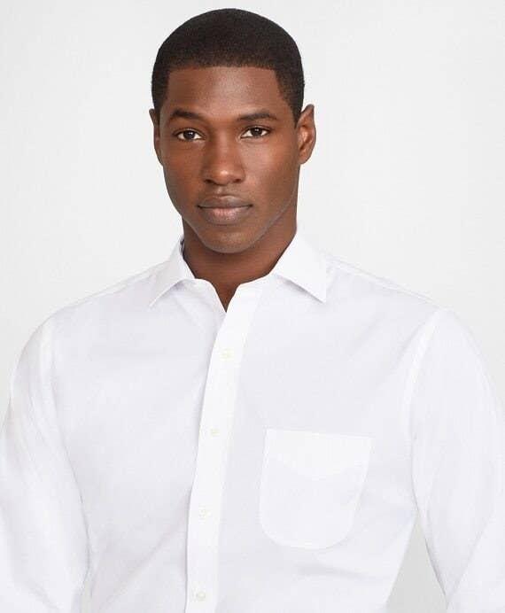 A model wearing a white button up dress shirt