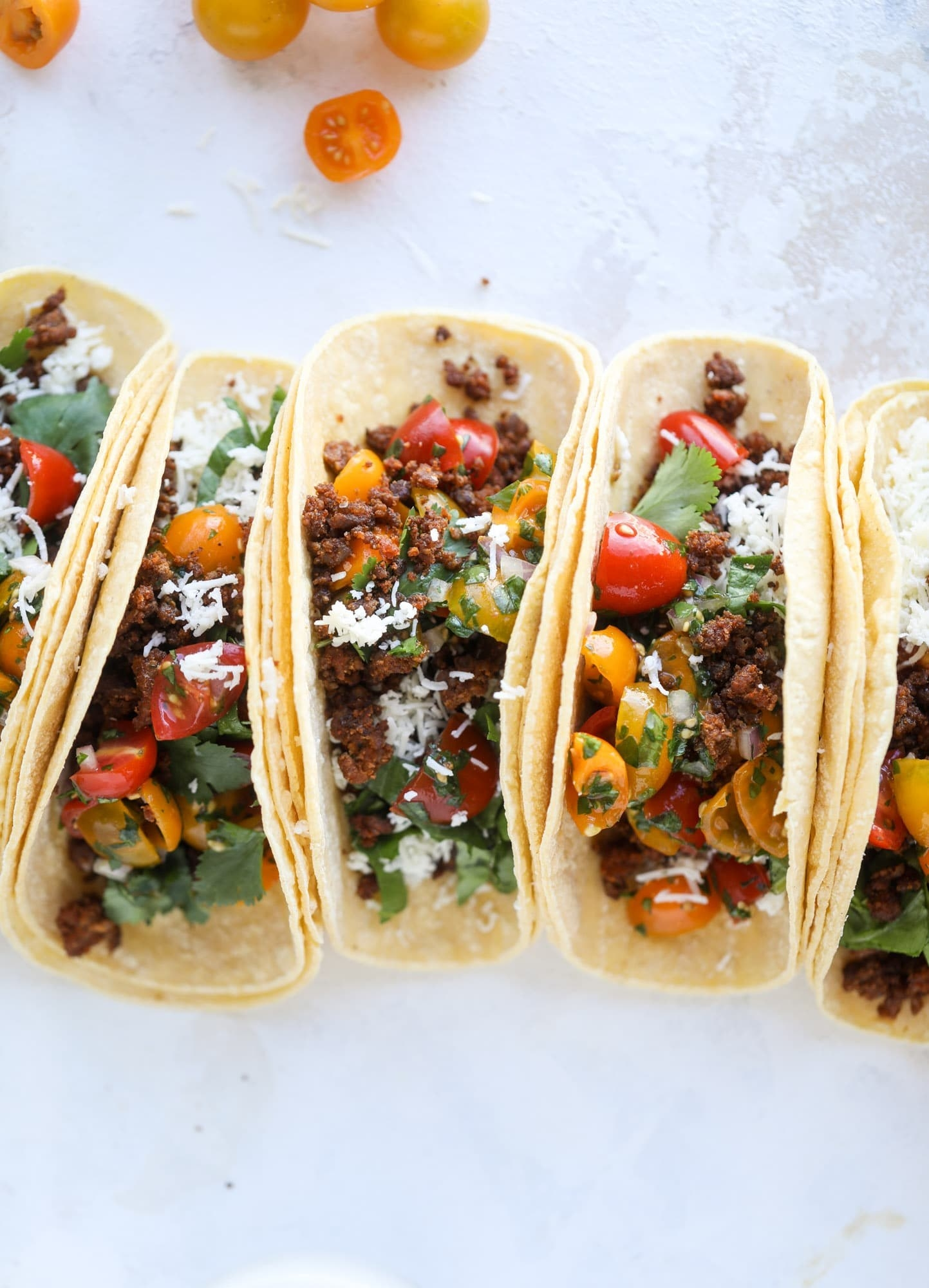 A handful of soft tortillas filled with ground beef, cherry tomatoes, onion, and cilantro.