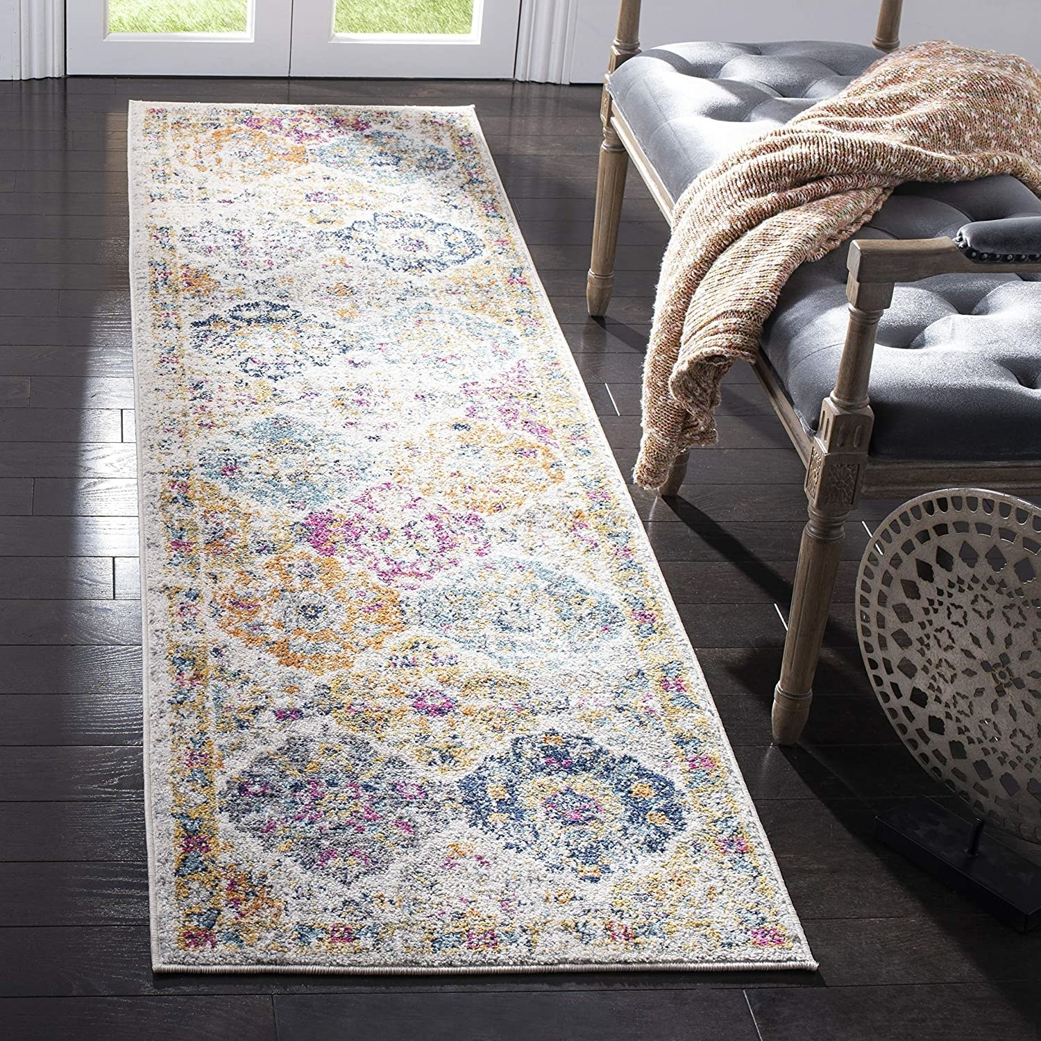 The rectangular runner with multi-color diamond-like pattern and border around it in a house