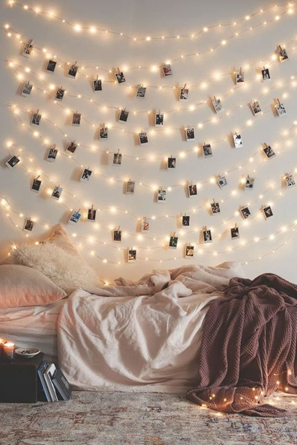 The lights strung up on a wall with Polaroid pictures clipped throughout in a bedroom