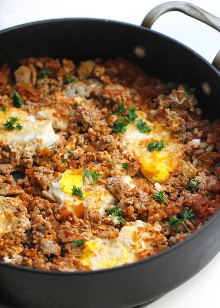A cast iron skillet filled with ground turkey, salsa, and baked eggs.