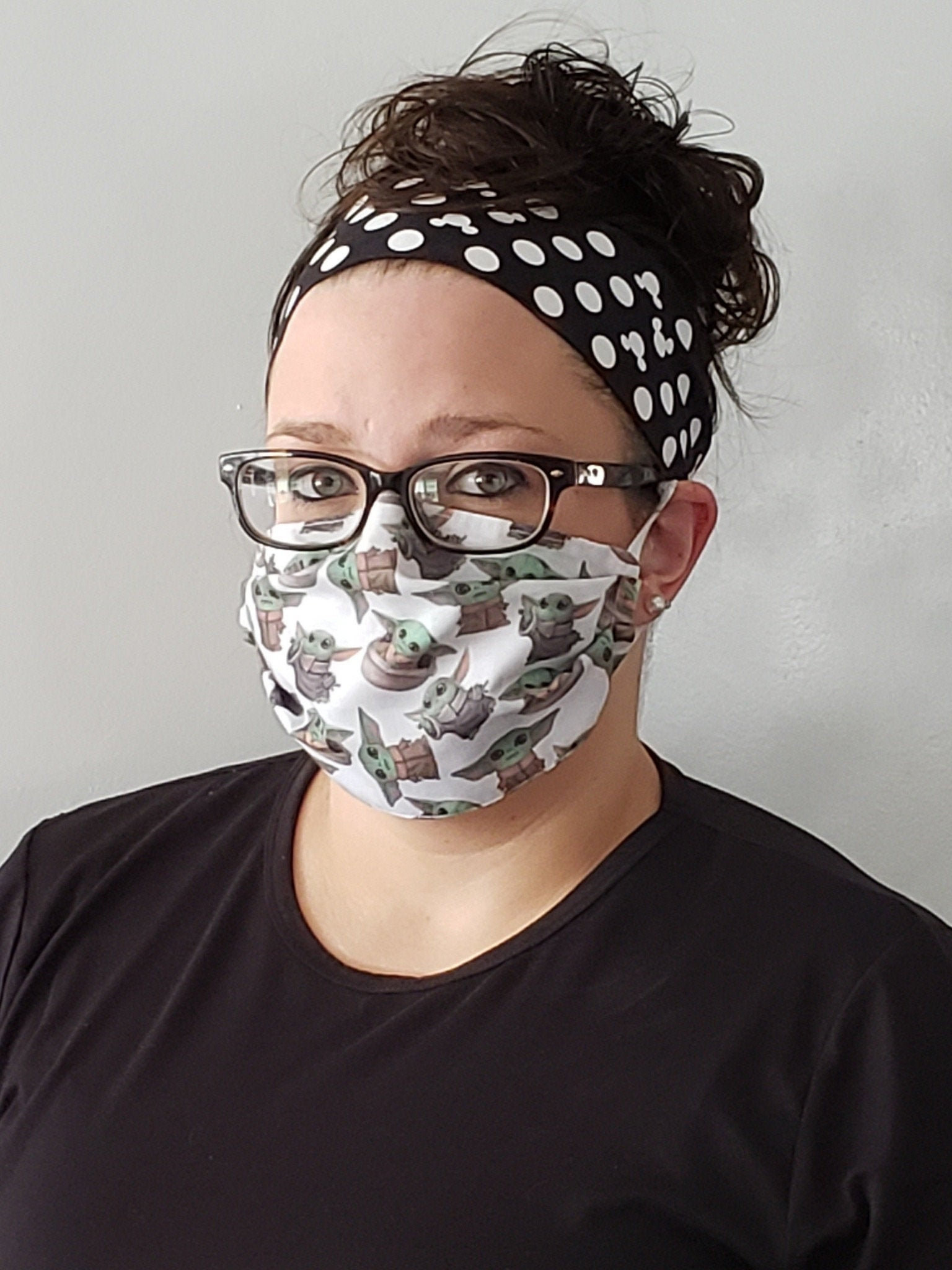 a model wearing a white mask with various illustrations of baby yoda on it