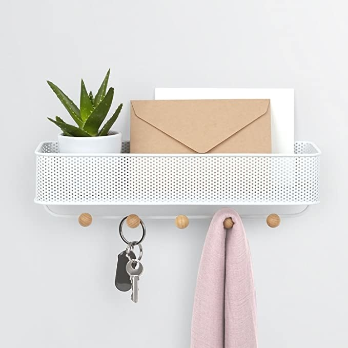Mail organizer with perforated metal bin and five hooks with wooden knobs under it on a wall