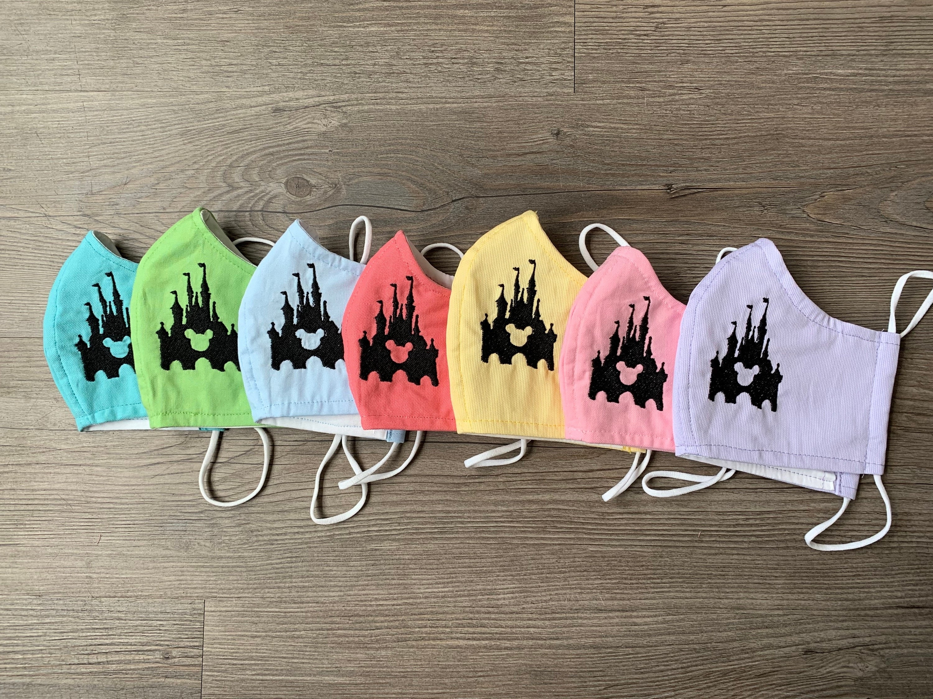 seven different colored disney face masks in a row, each have cinderella castle on it with a mickey head shape in the middle