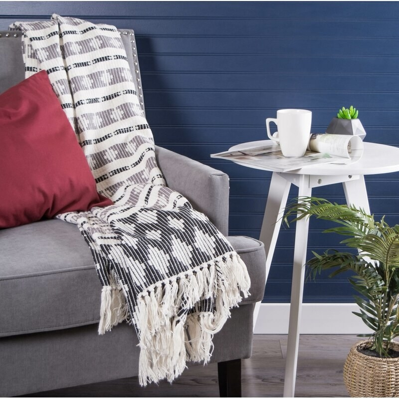 A gray and white throw blanket with alternating stripes and diamond patterns and white tassels laying over a gray armchair