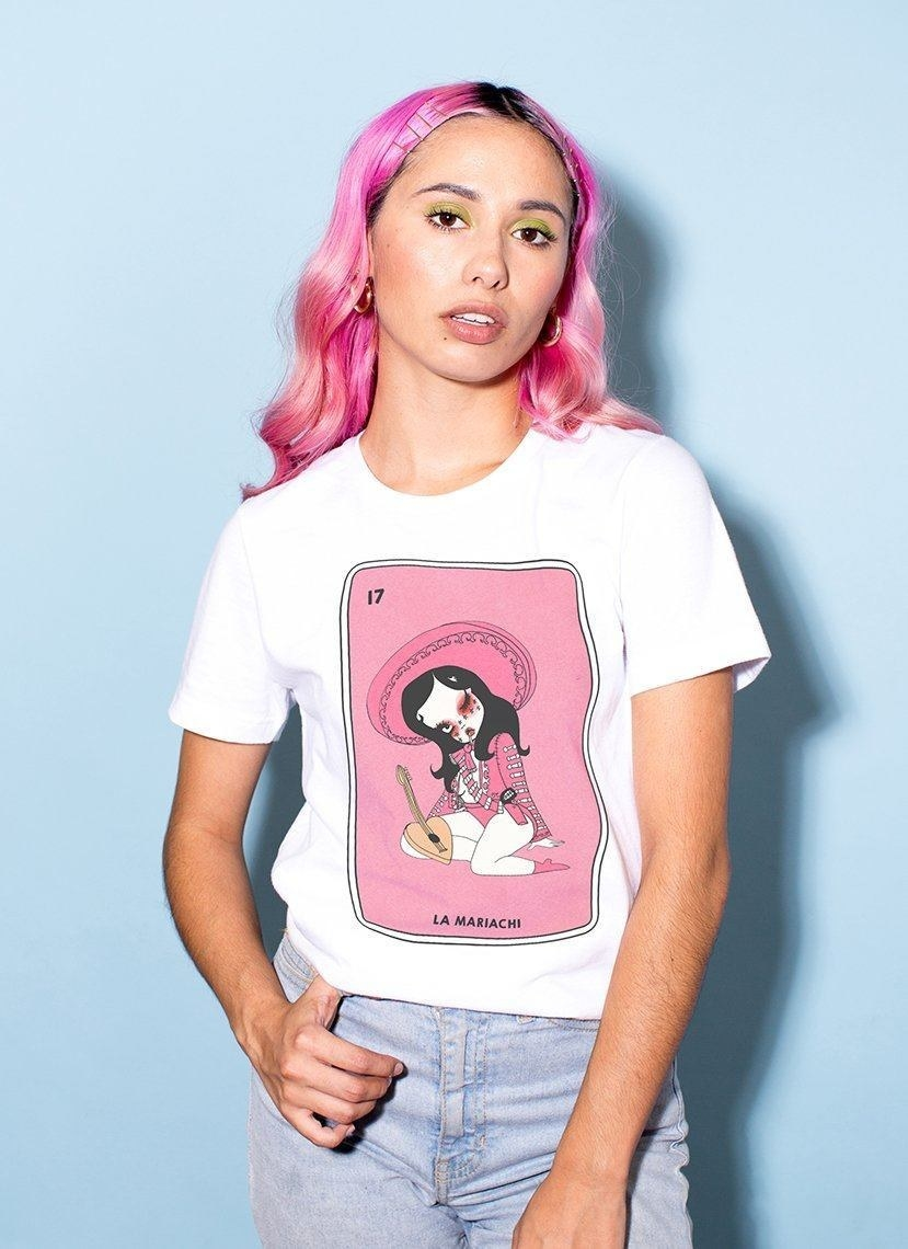 model wearing shirt with pink loteria-style shirt with cute mariachi player on it