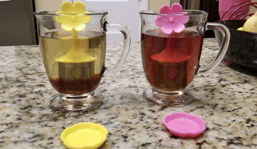 Clear mugs with yellow and pink floral tea infusers inside of them