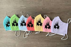 a row of various colored masks with a castle embroidered on it and the shape of mickey inside the castle