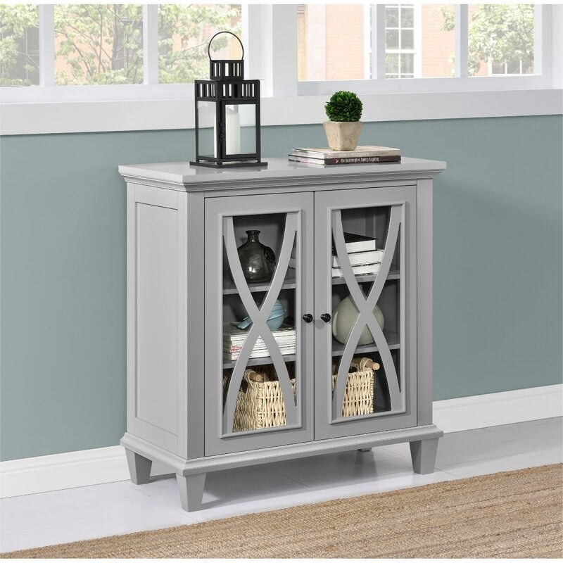 A gray cabinet with glass window doors