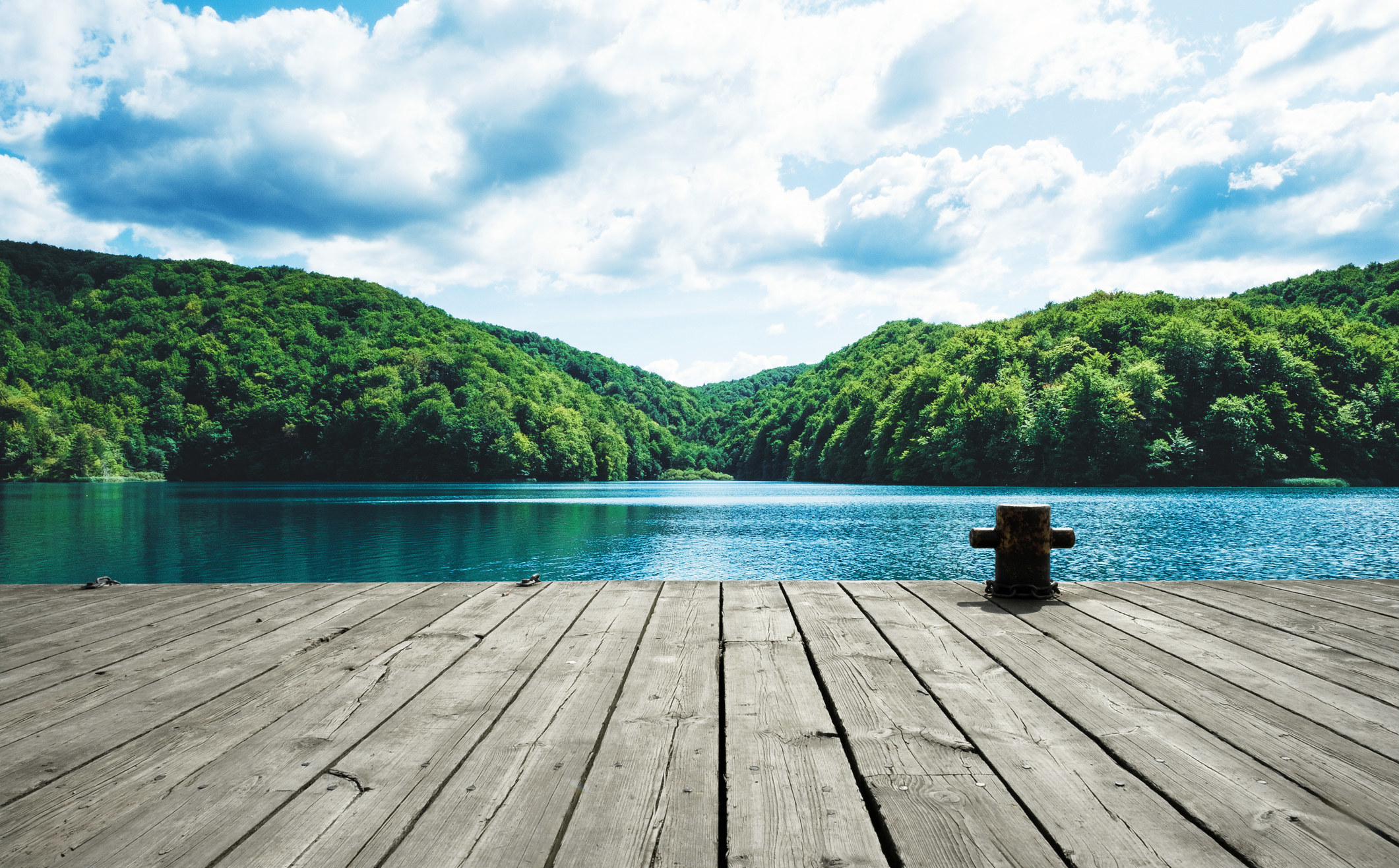 A deck and a lake in the distance.