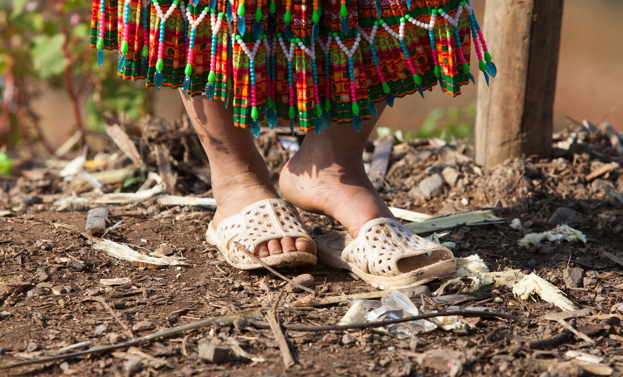 A child's feet in sandals standing on dirt.