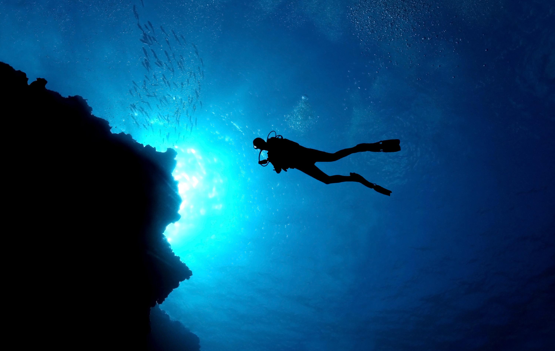 A silhouette of a scuba diver swimming.