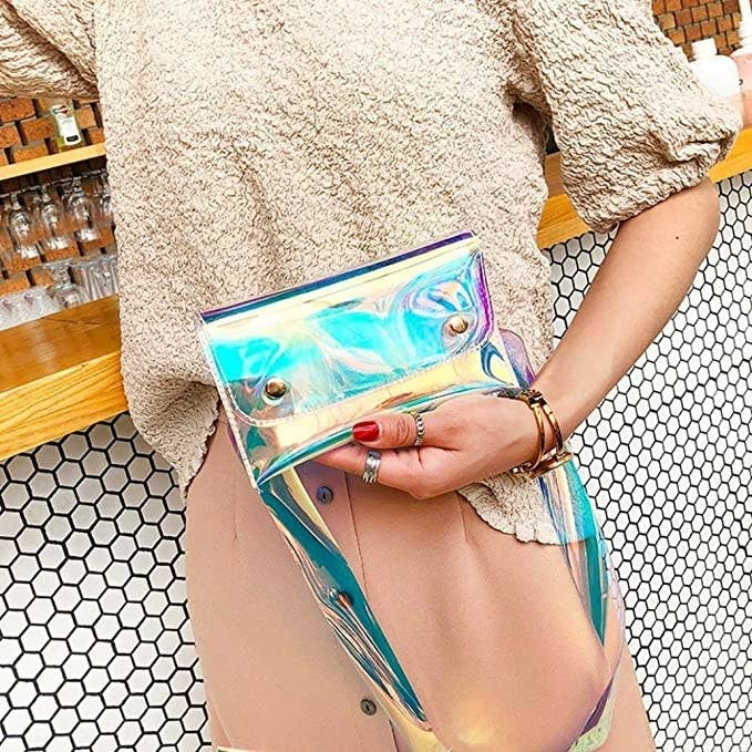 stylish person holding a holographic translucent purse the size of an envelope with a strap