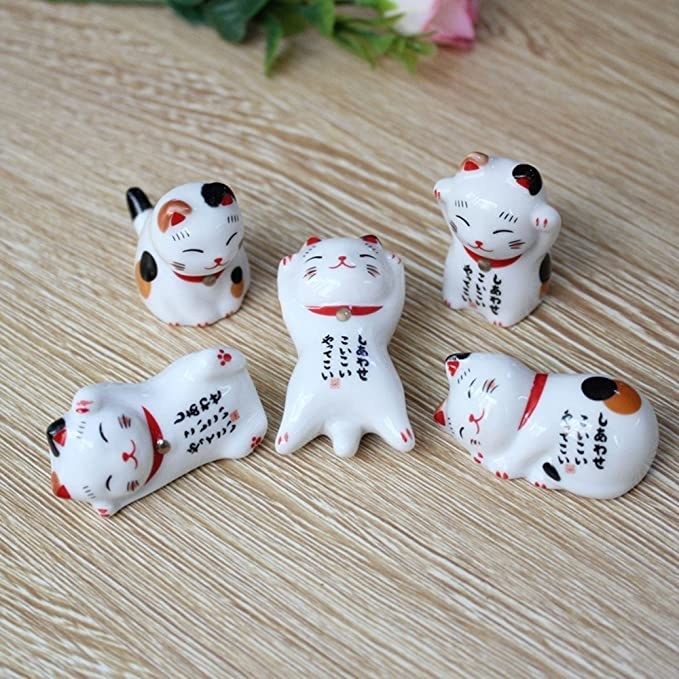 tabletop with five little cats made for resting your chopsticks